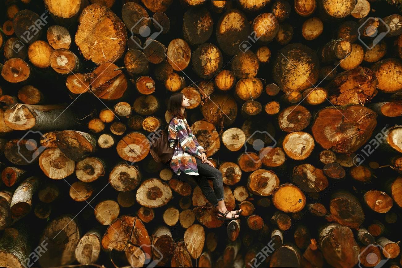 Elegante donna hipster con zaino seduto al mucchio di legna da ardere, relax e pensare, momento atmosferico, scala umana, spazio per il testo Archivio Fotografico - 75725767