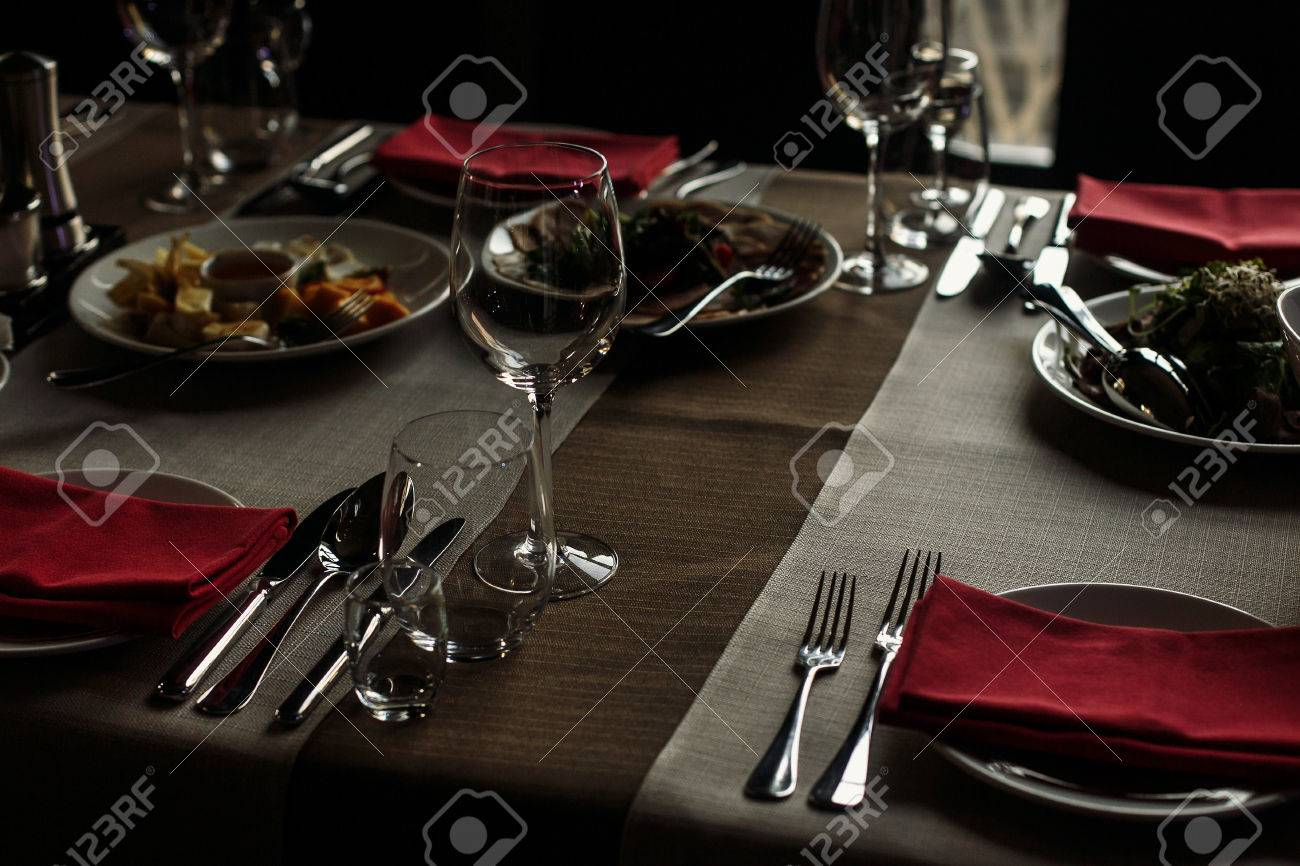 Luxury Wine Glasses And Silver Tableware Near Plates With Red Napkins Close Up