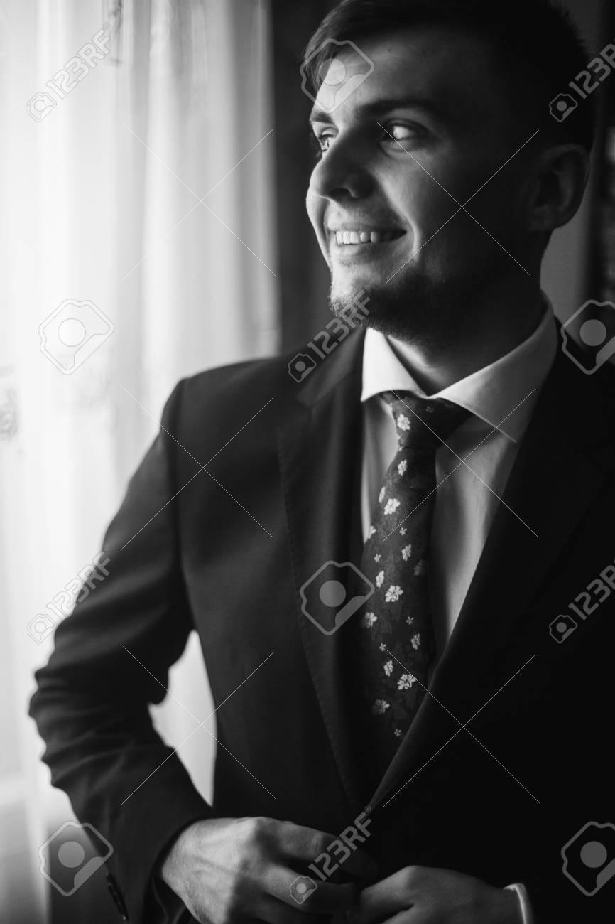 bas prix 95a2a 8f101 Beau marié en chemise blanche avec une cravate rouge boutonnant costume  noir, préparation du mariage du matin, homme d'affaires en costume  regardant ...