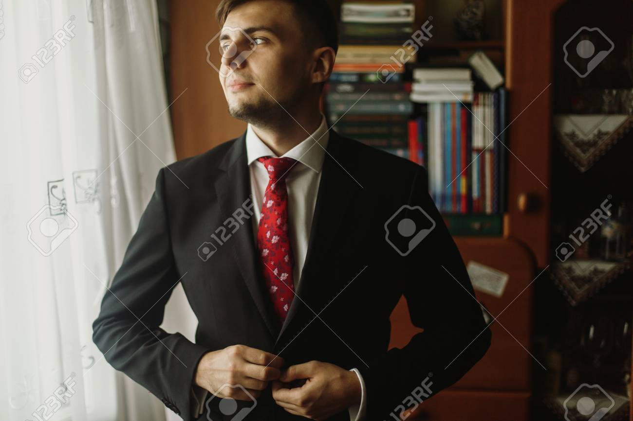 Handsome Groom In White Shirt With Red Tie Buttoning Up Black