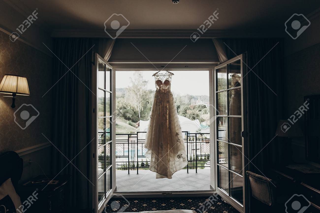 3c1090a2a7 luxury wedding dress hanging on window in a hotel room. silhouette of amazing  bride s gown