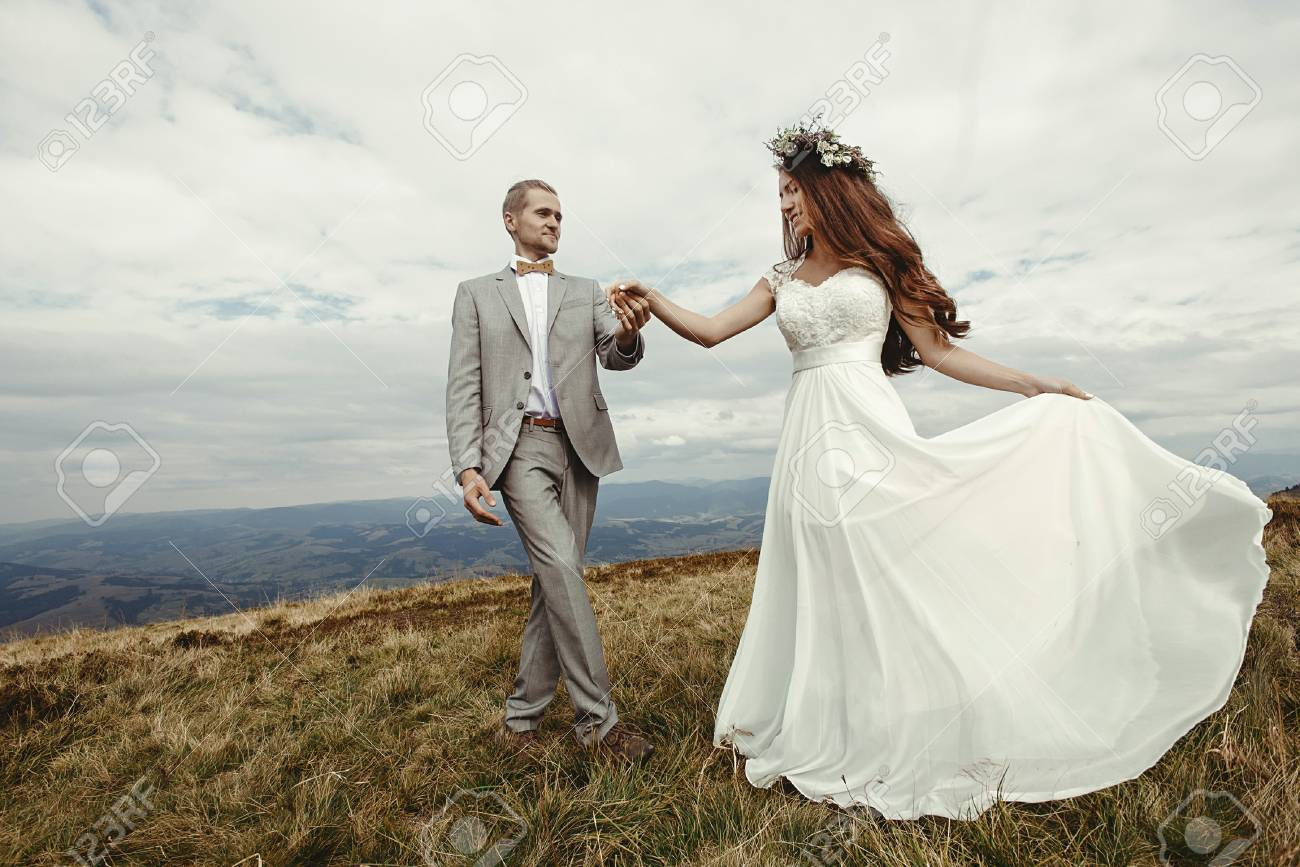 Happy Gorgeous Bride And Groom Holding Hands Dancing In Sun Light Boho Wedding Couple