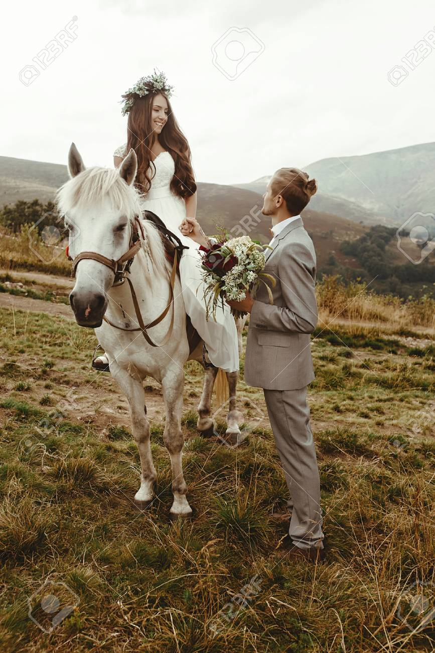 Gorgeous Bride Riding A White Horse And Stylish Groom Boho Stock Photo Picture And Royalty Free Image Image 75745317