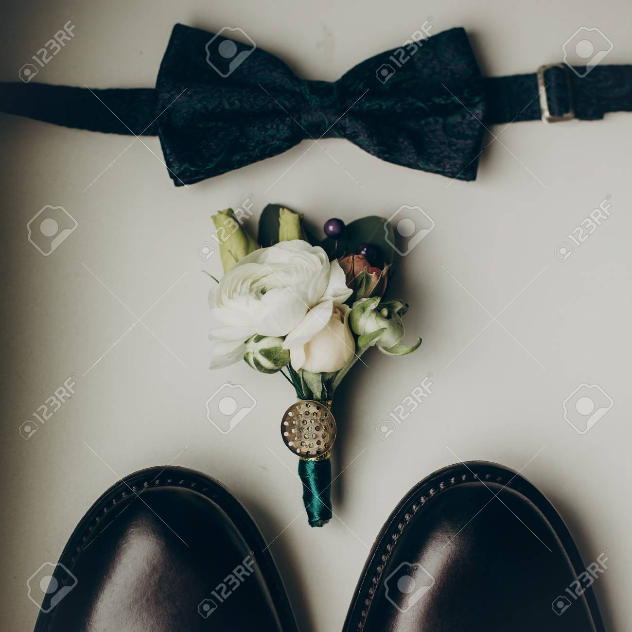 5c94db3b37d Stock Photo - stylish wedding bow tie with modern flowers bouquet and shoes  on wooden background top view. rustic wedding morning preparation. groom  set. ...