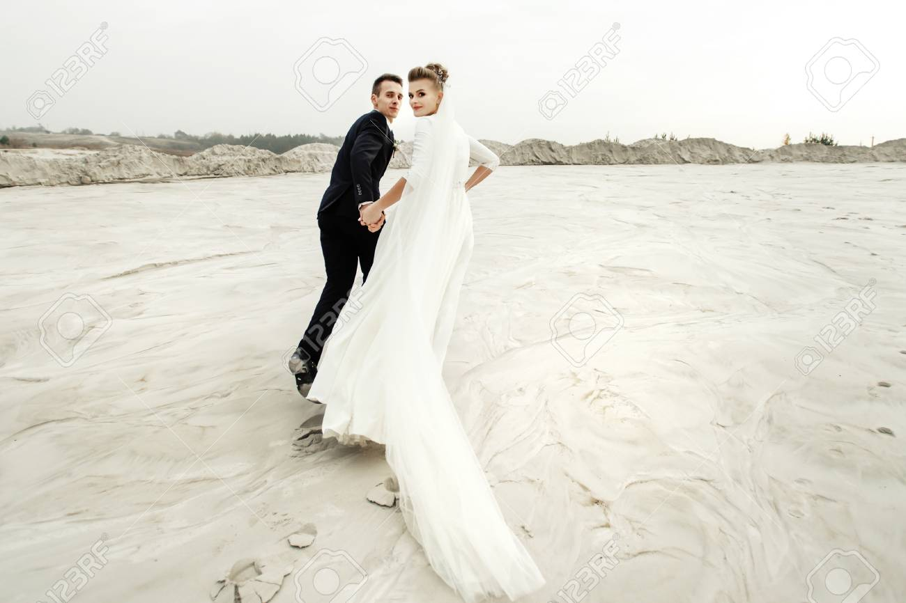 Awe Inspiring Happy Bride And Groom Running And Having Fun At Sandy Beach Lake Download Free Architecture Designs Scobabritishbridgeorg