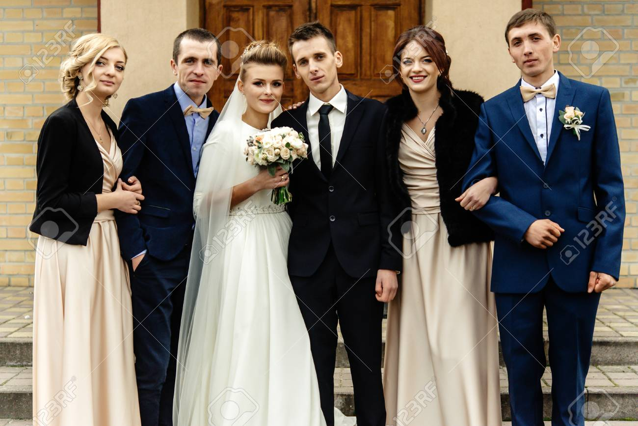 Bride And Groom With Happy Groomsman And Bridesmaid Posing At