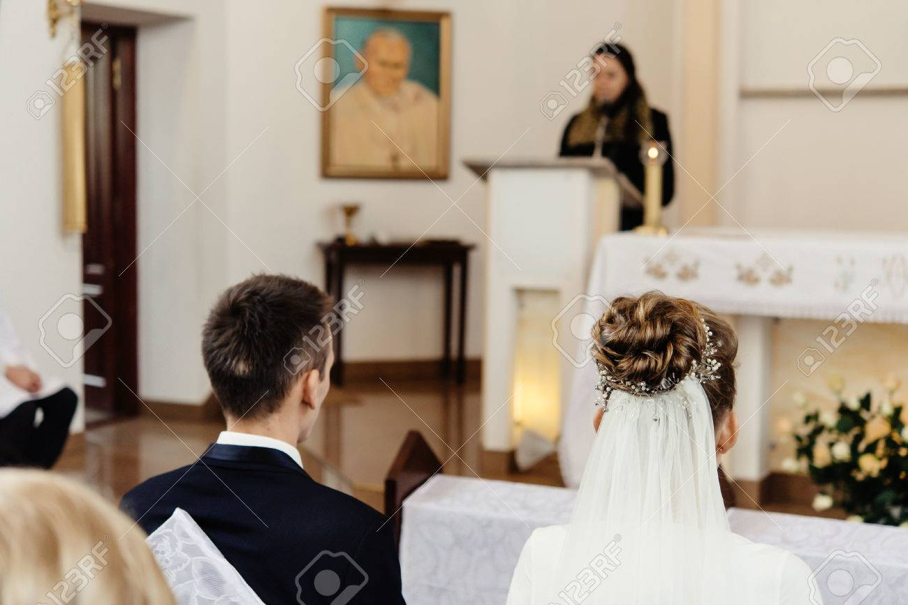 Happy stylish bride and elegant groom sitting at catholic wedding happy stylish bride and elegant groom sitting at catholic wedding ceremony at church stock photo junglespirit Image collections