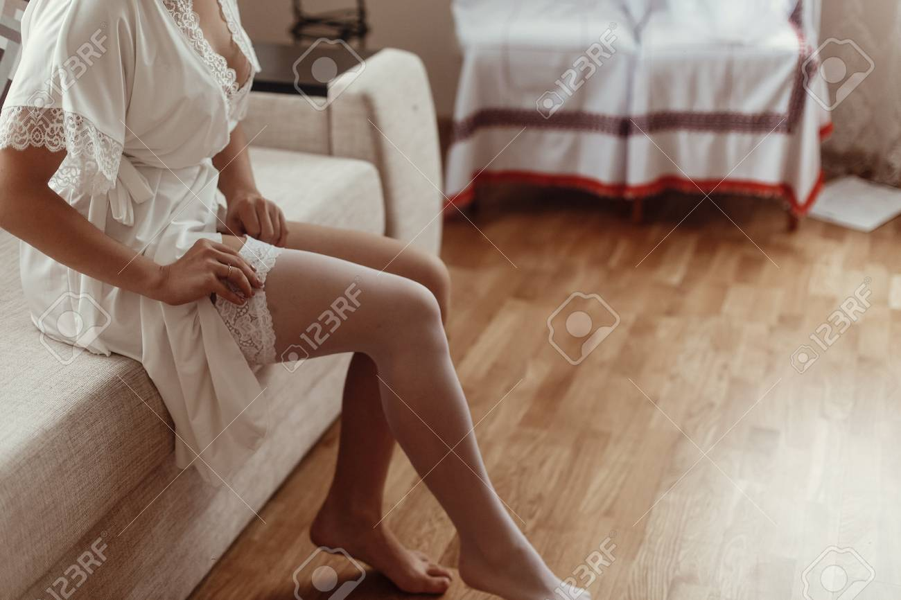 04770ce2b Bride In Silk Robe Putting On Stockings