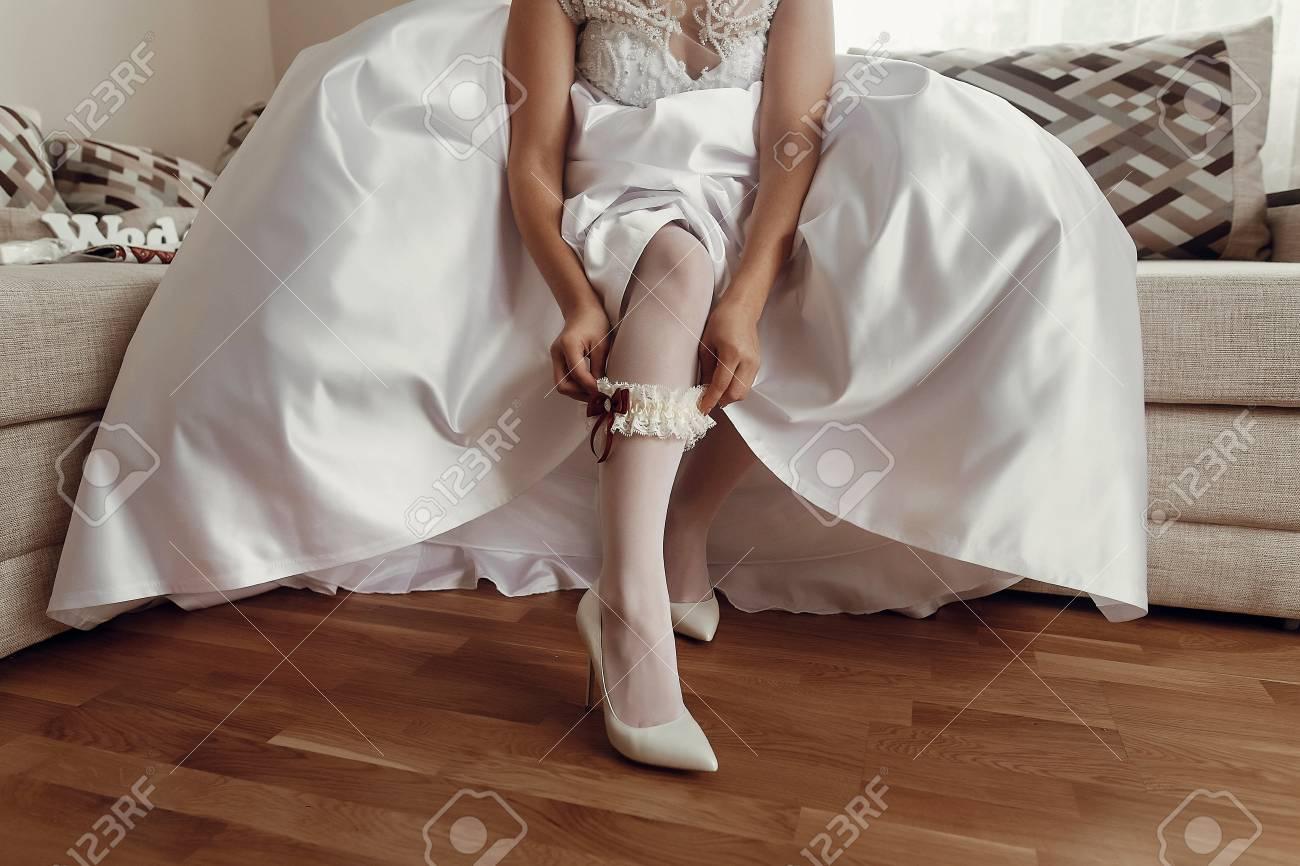 6c8e19e4a Bride In Wedding Dress Putting On Stockings Silk Garter