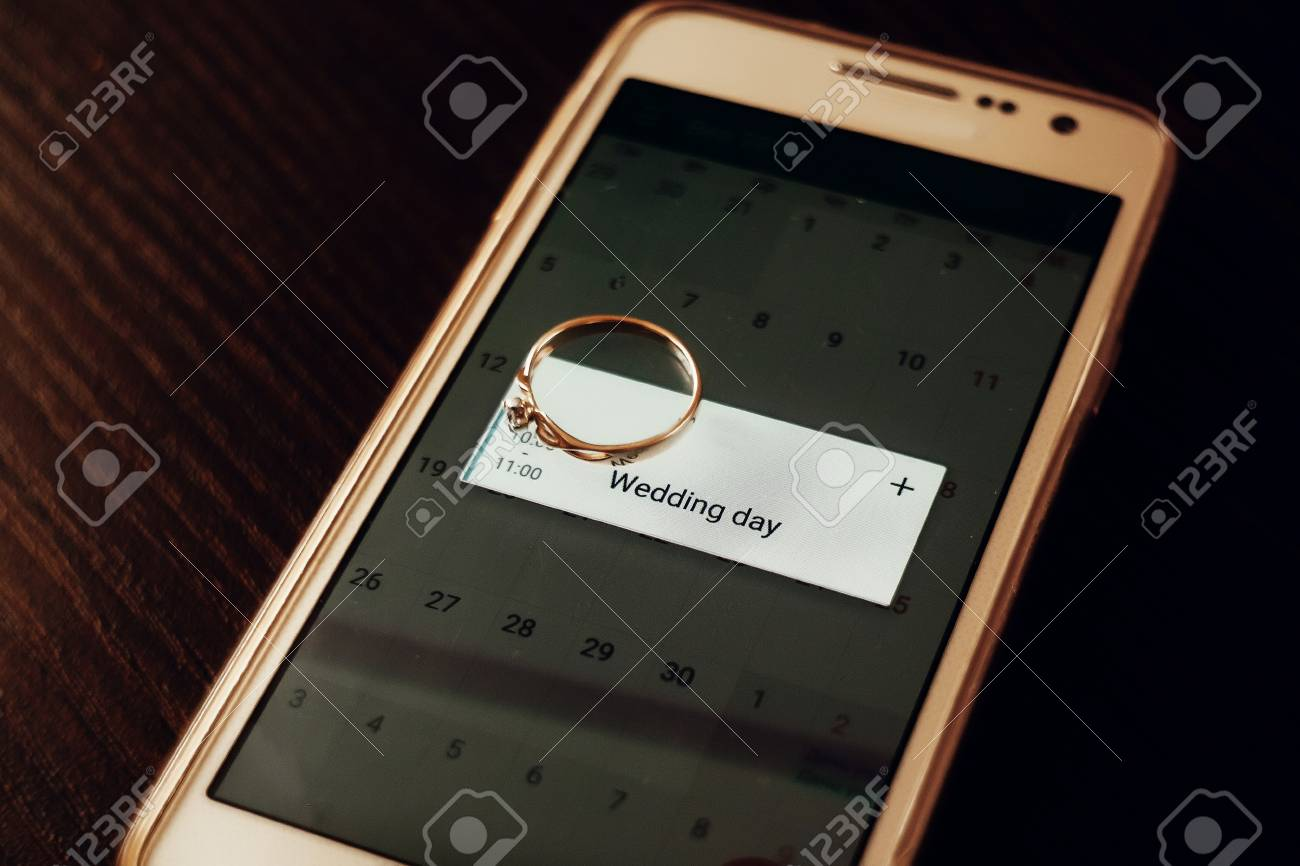 Golden Engagement Ring On Phone With Calendar With Wedding Day