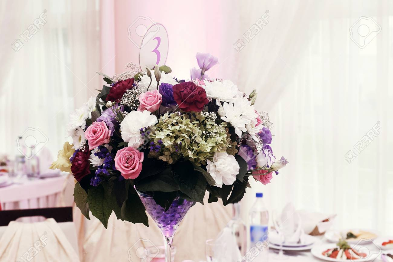 flowers in vases and numbers of setting at wedding tables with food in restaurant luxury
