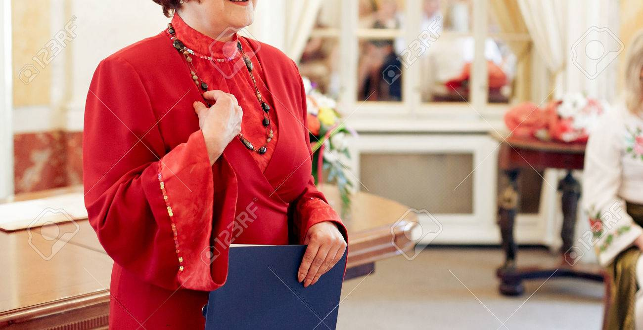 Old Woman Ceremony Master Perfoming Speech In Red Dress At Wedding Reception Stock Photo