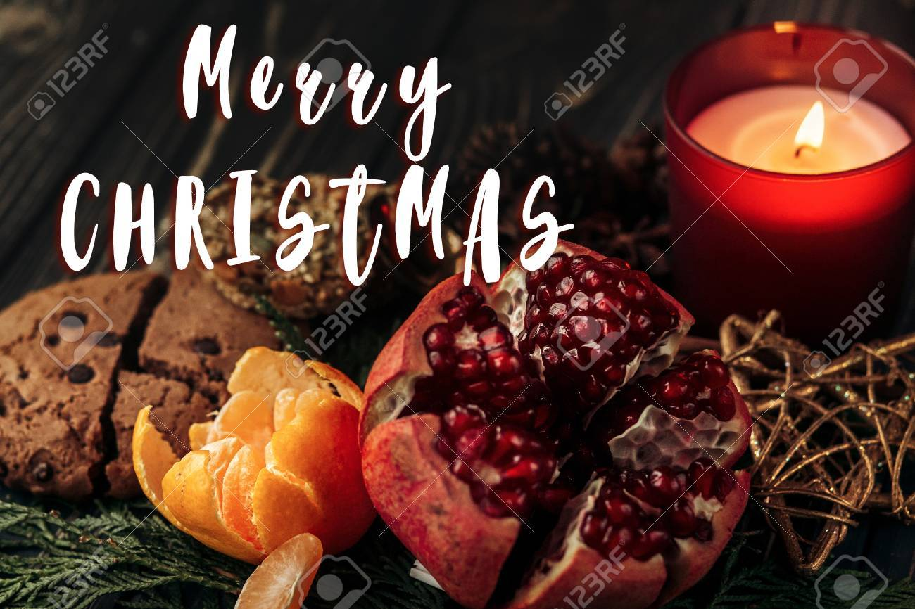 Merry Christmas Text Sign On Stylish Rustic Wallpaper Candle Garnet Cookies Fruits Wooden Background With