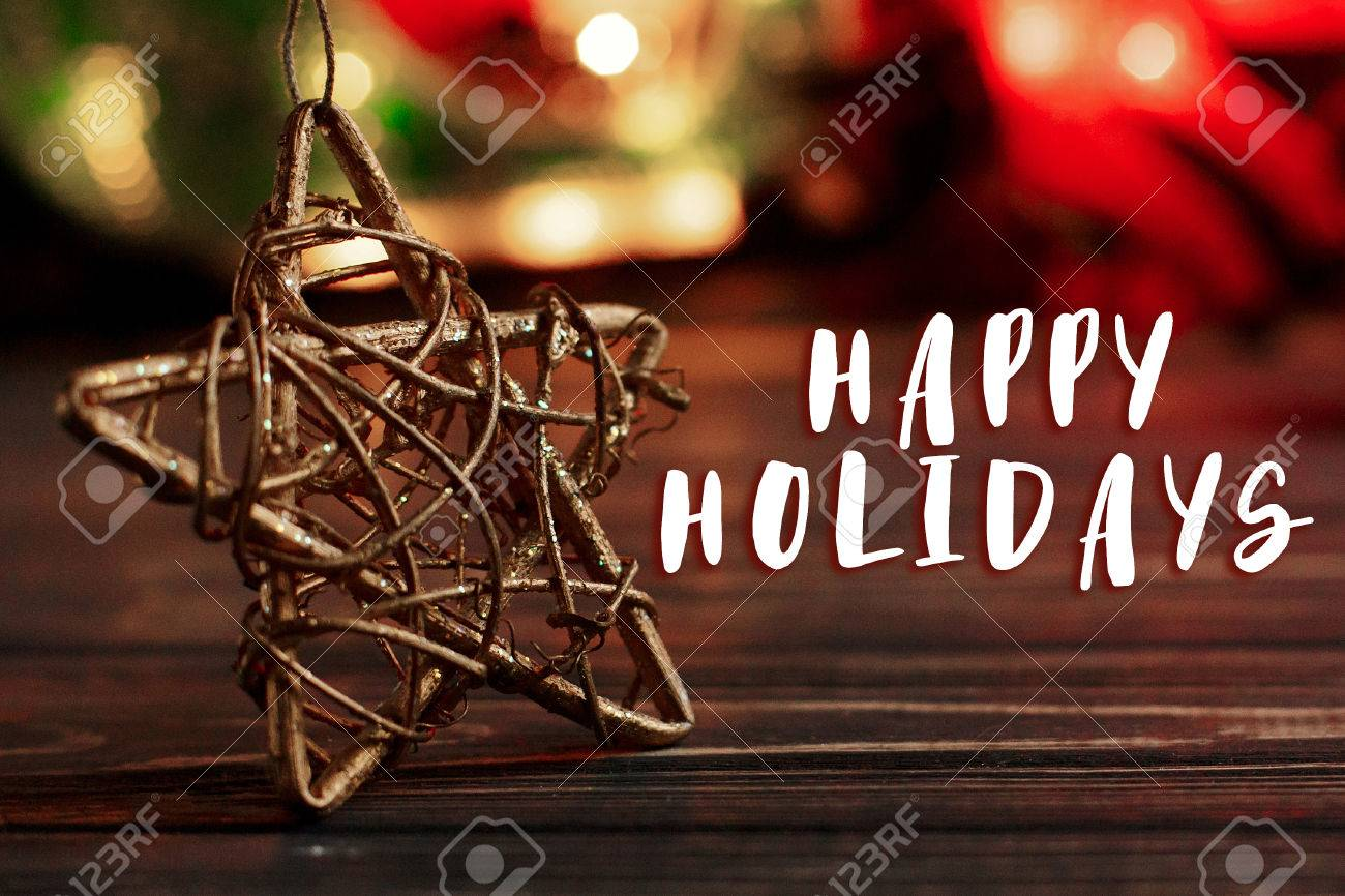 504a74e7fb033 happy holidays text sign on christmas golden star on background of garland  lights on black rustic