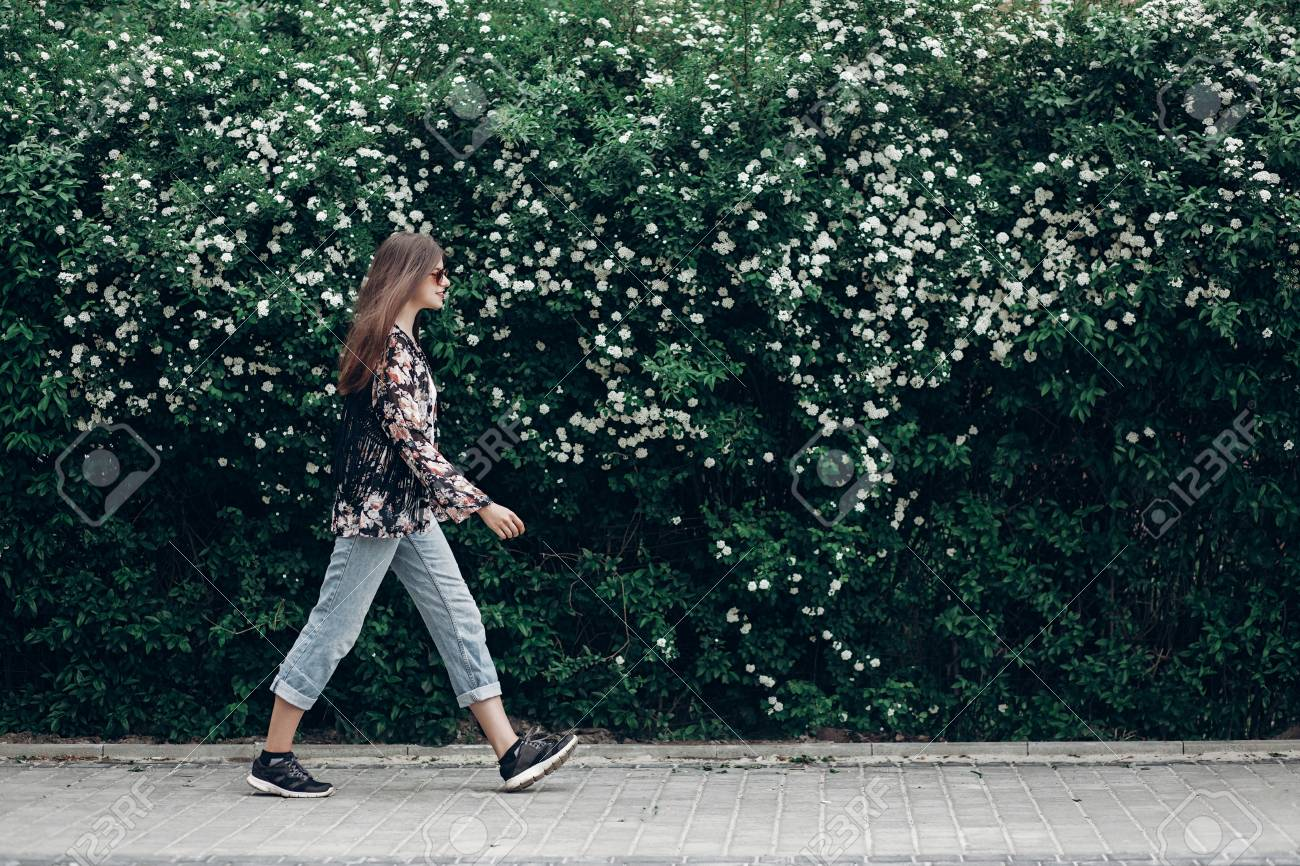 Hipster Woman In Sunglasses Walking On Background Of Blooming