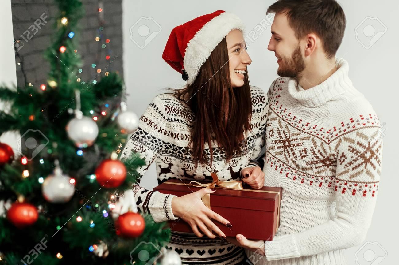 Regali Di Natale Romantici.Uomo Bello Che Da Regalo Di Natale Alla Sua Bella Donna In Cappello Rosso Di Santa Vicino All Albero Di Natale Decorato Coppie Romantiche Che