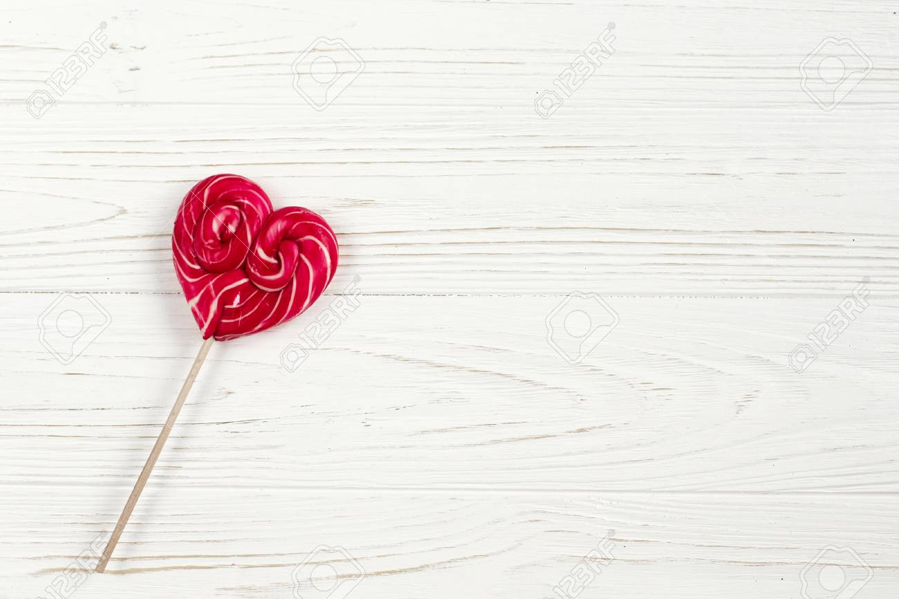 heart candy lollipop on white rustic wooden background  space