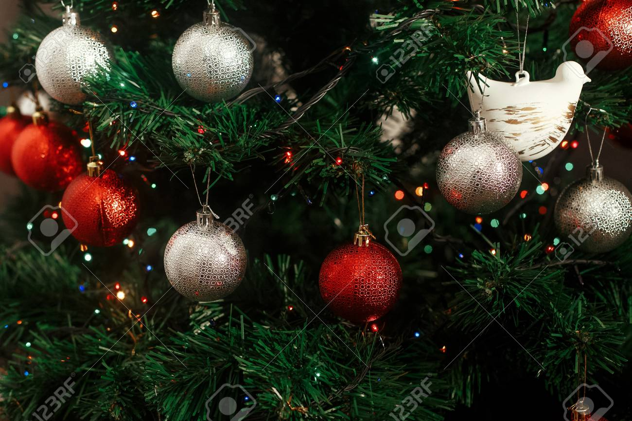 Silver And Red Christmas Ornaments Hanging From Green Christmas