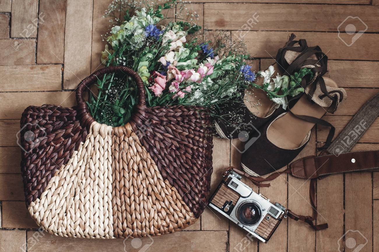23e4f669fb9 beautiful wildflowers in wicker bag and film camera and hipster woman shoes  on rustic wooden background