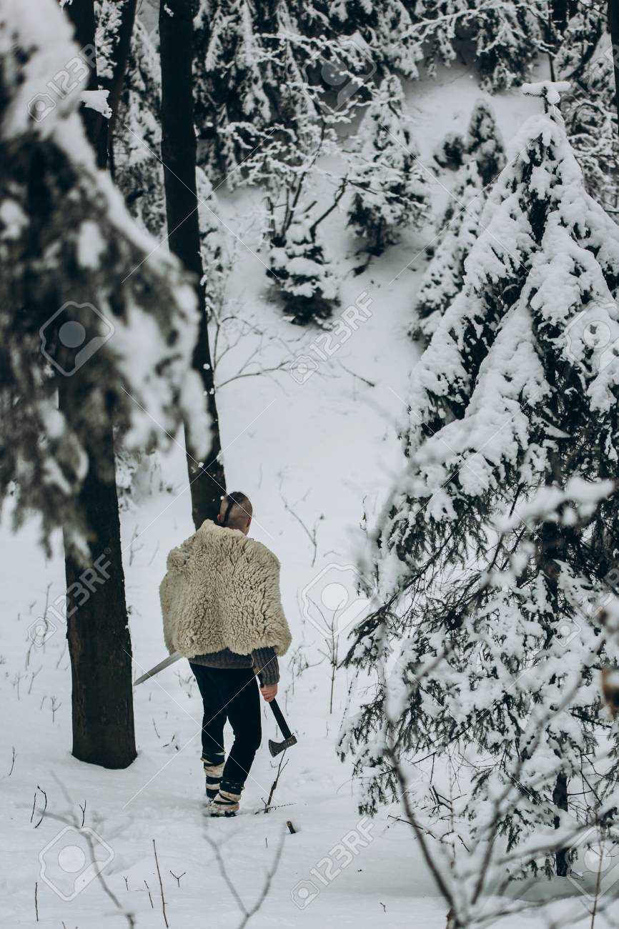 Ancient viking hunter walking in snow winter forest with steel