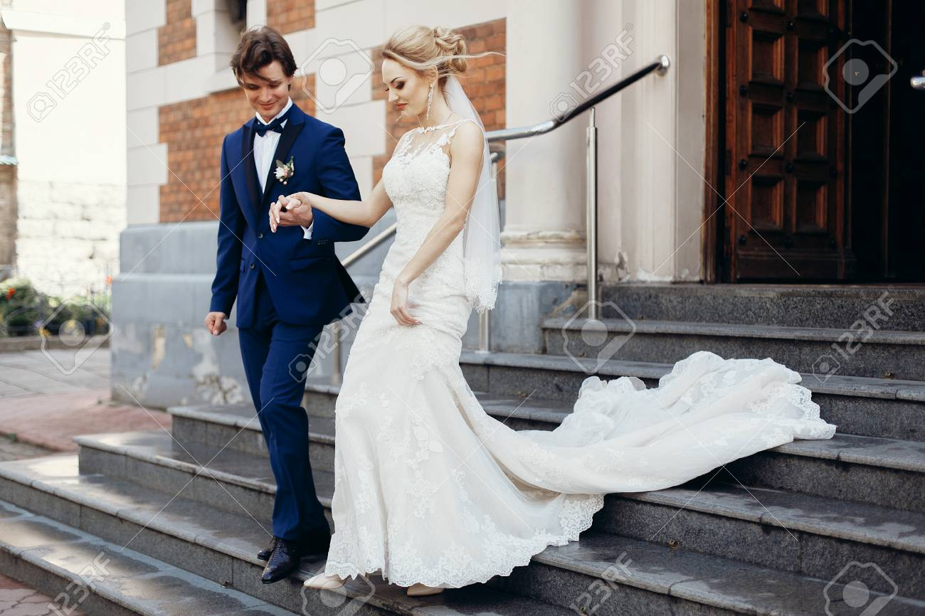 Beautiful Newlywed Couple Walking Out Of Church After Wedding Ceremony In Christian Happy