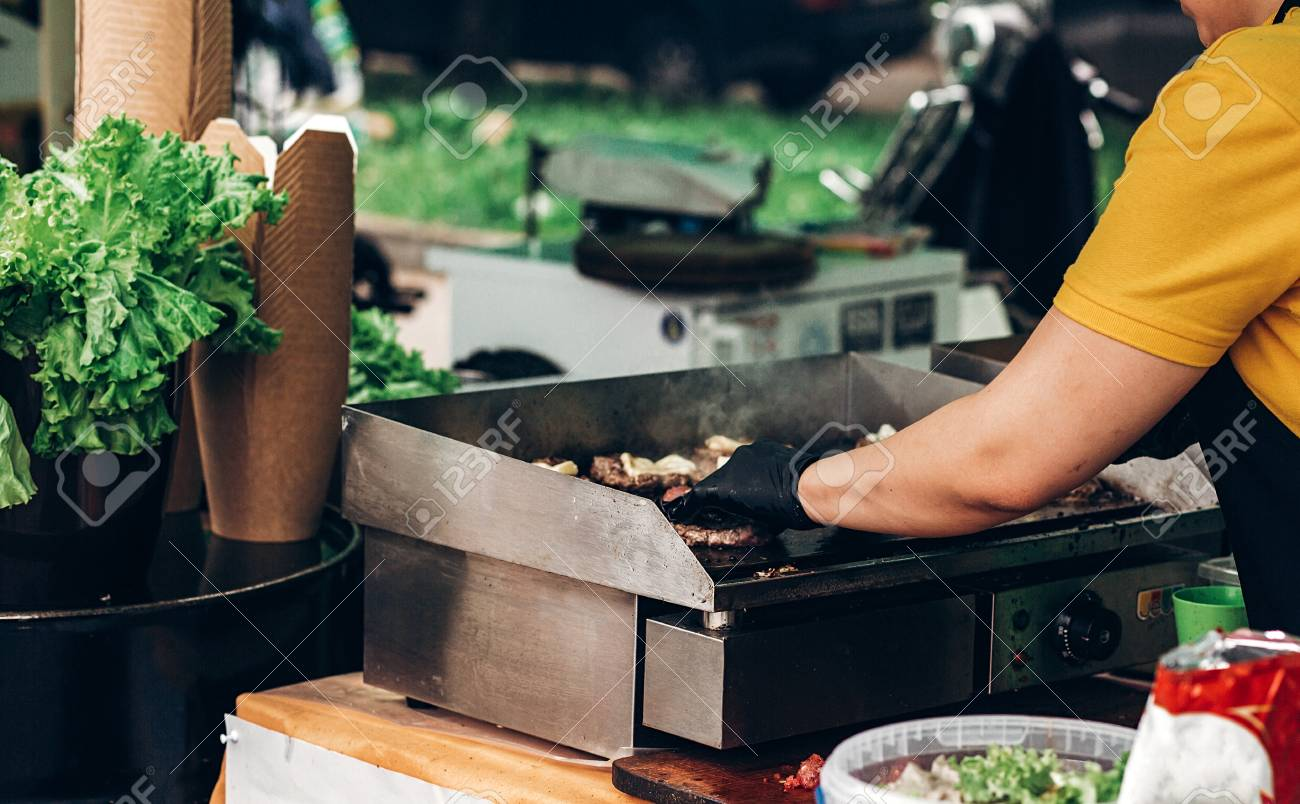 man making burgers, roasting meat and vegetables on grill. chef