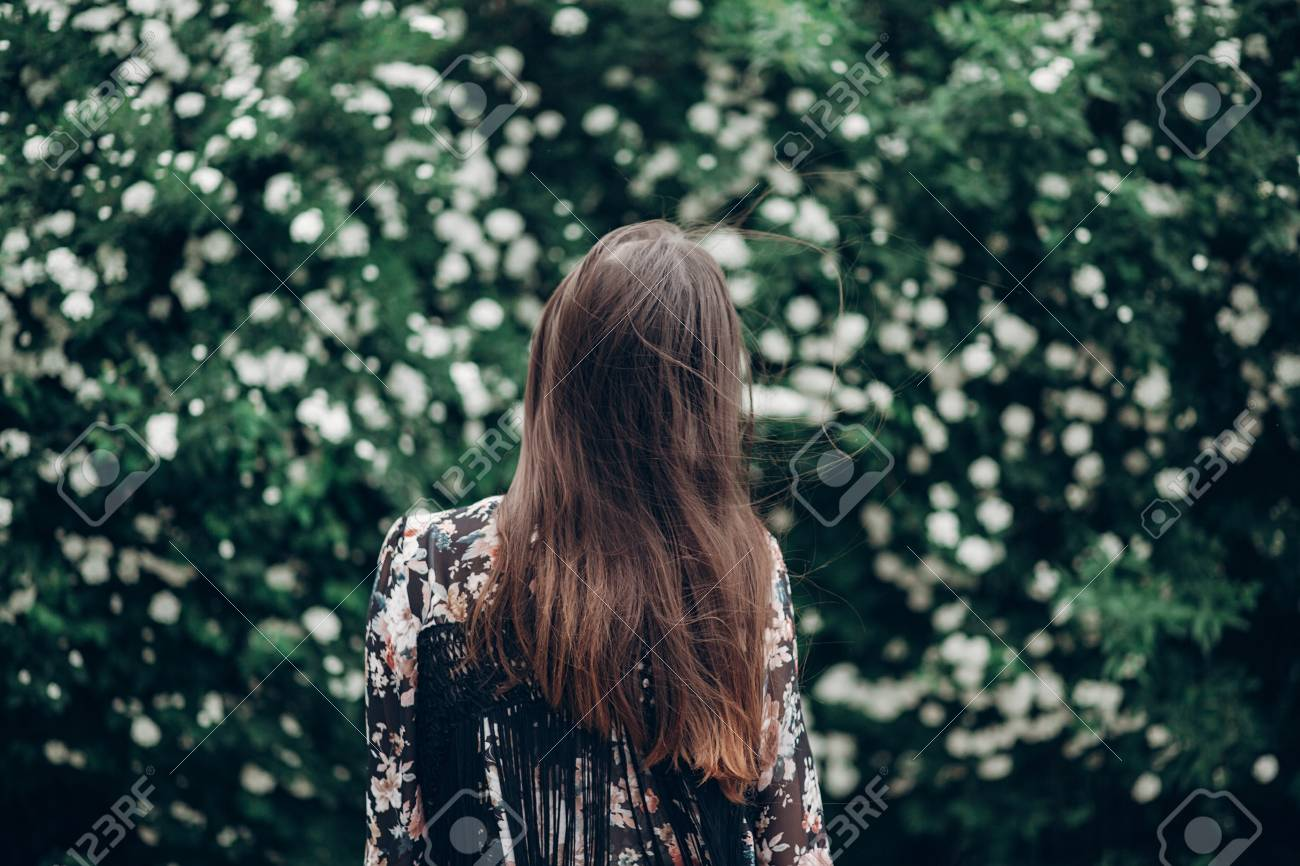 Back Of Hipster Woman Posing On Background Of Blooming Bush With