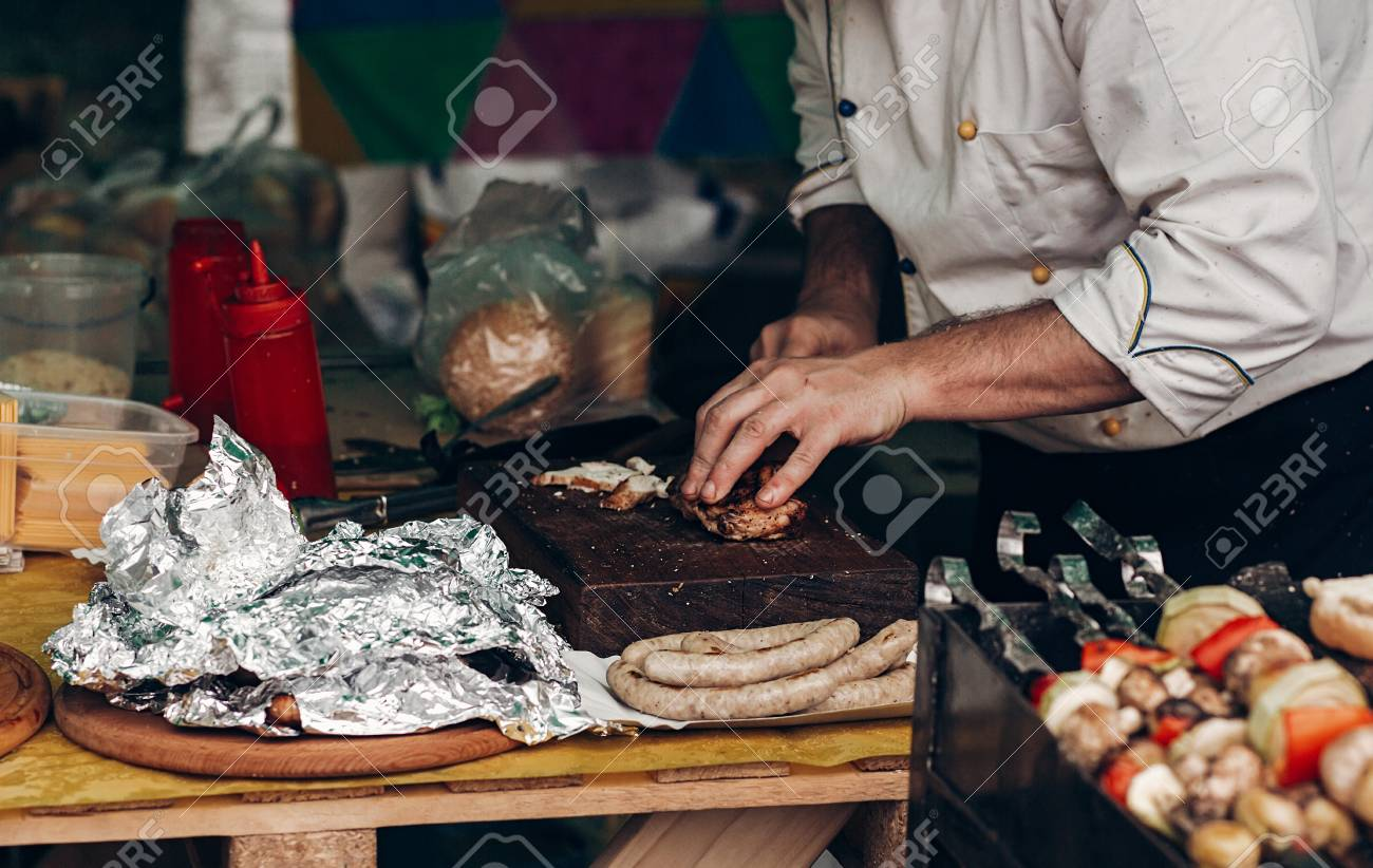man roasting meat and vegetables and sausages on grill. chef.. stock
