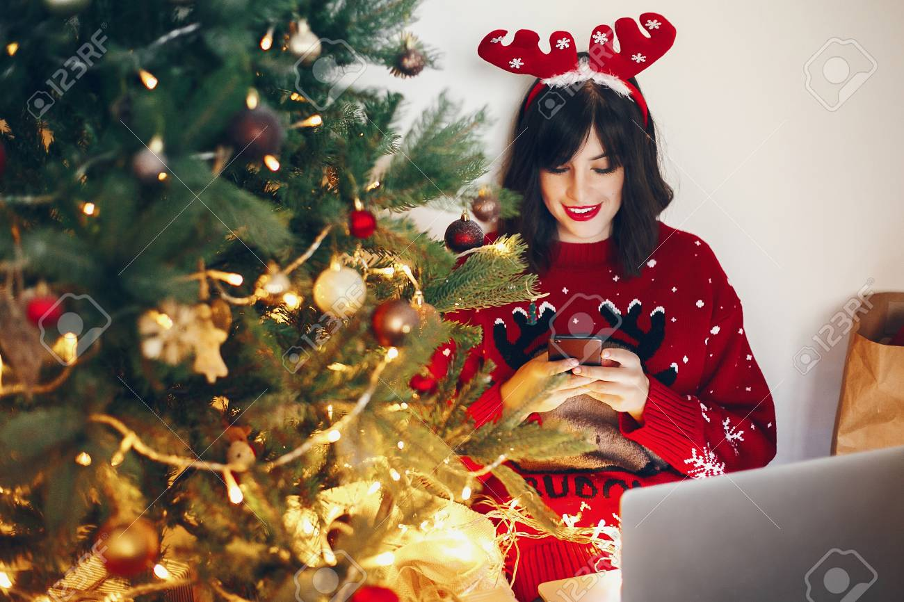 Stylish Woman In Reindeer Hat Holding Phone And Laptop Under