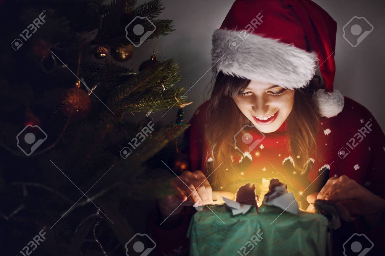 Happy woman in santa hat opening gift box at christmas tree lights happy woman in santa hat opening gift box at christmas tree lights magic light m4hsunfo Images
