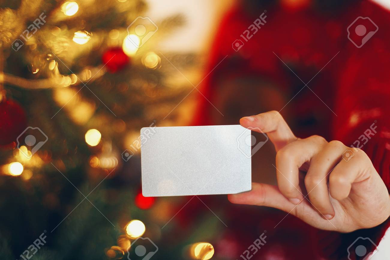 Hand Holding Empty Credit Card At Beautiful Christmas Tree Lights
