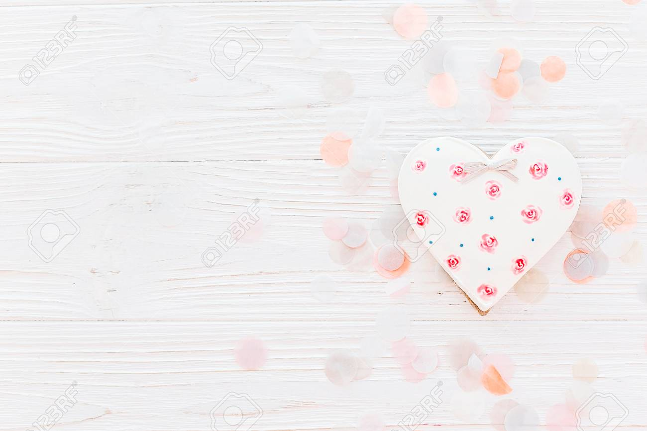 Pink Cookie Heart On White Rustic Wooden Background With Confetti Flat Lay In Soft Light