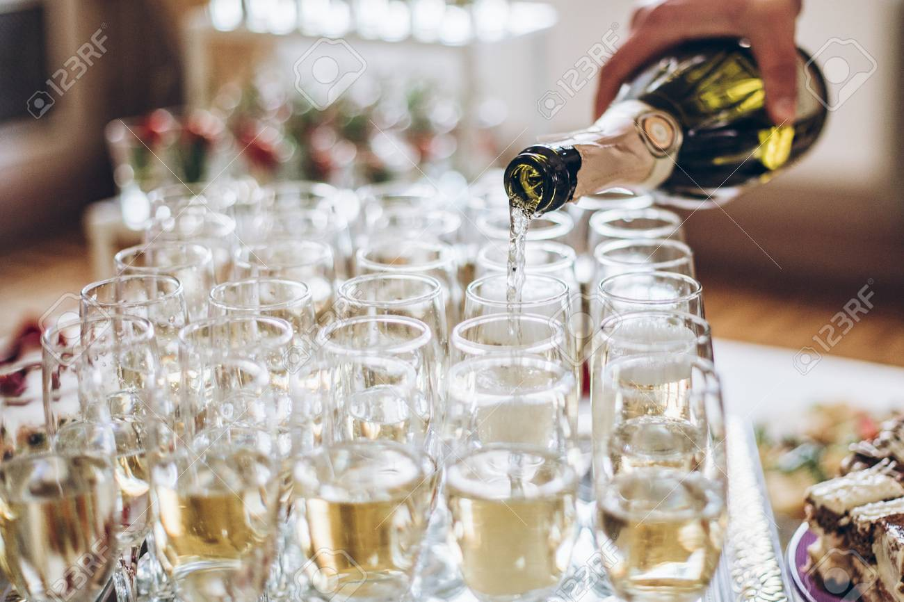champagne golden glasses. waiter pouring champagne in stylish glasses at luxury wedding reception. rich celebration. - 98773172