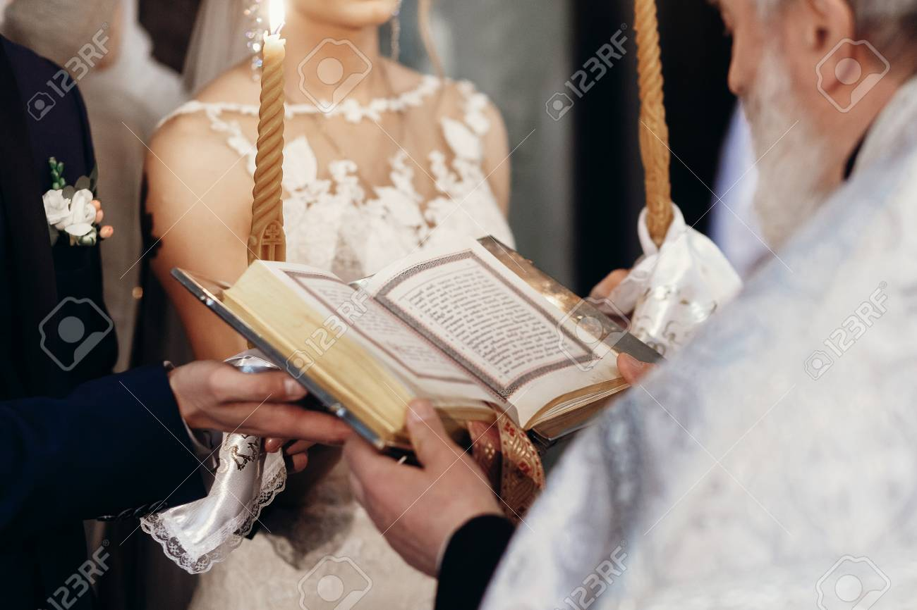Priest Holding Gospel Stylish Bride And Groom Holding Bible With Priest At Holy Matrimony In Church Spiritual Love Couple During Wedding Ceremony