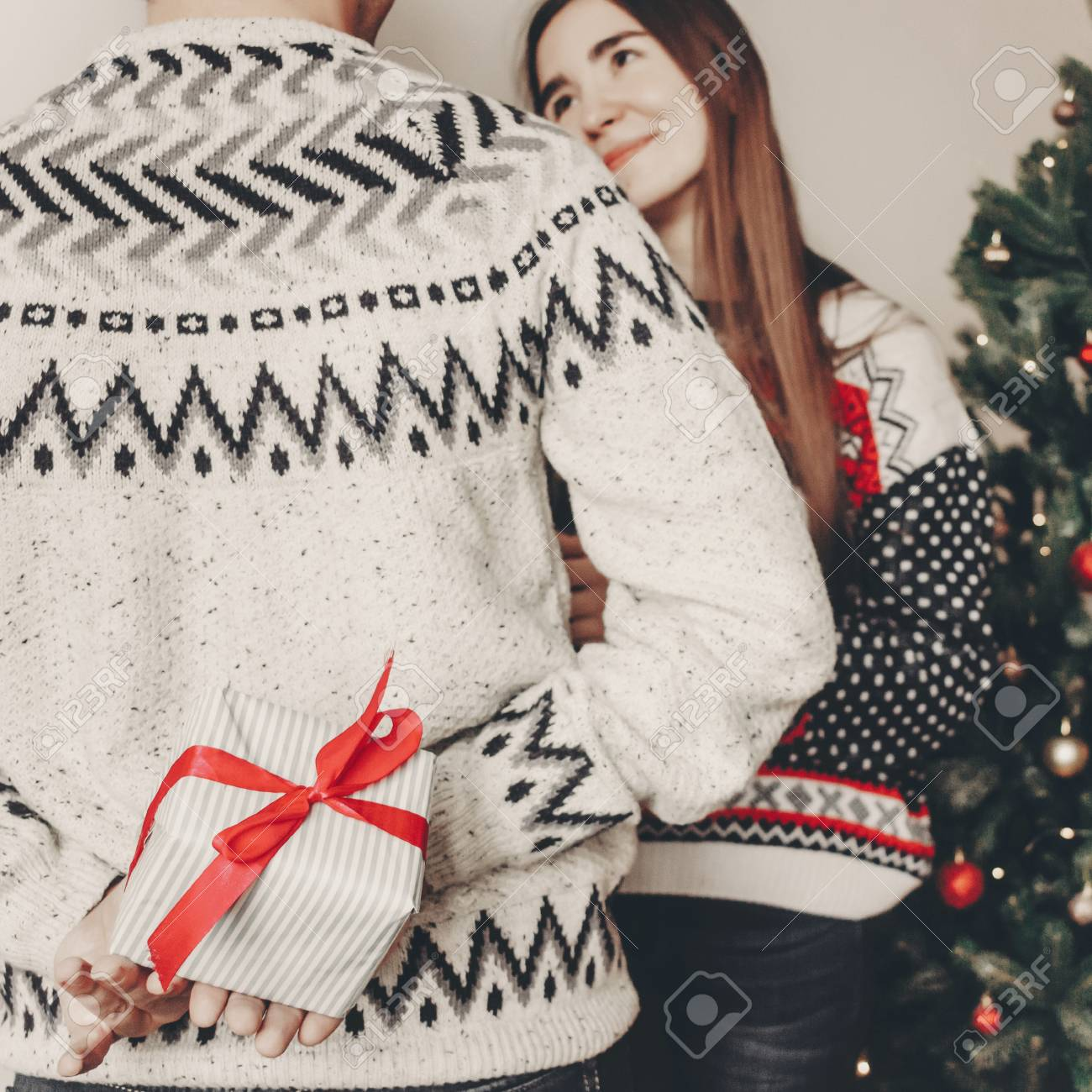 Happy Family In Stylish Sweaters Exchanging Gifts In Festive.. Stock ...