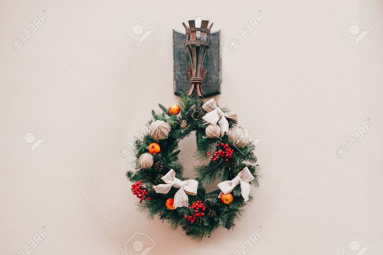 Stylish christmas wreath with red berries,bows and ornaments, pine cones, branches on building in european city street. Festive decor in city center, winter holidays. - 109911644
