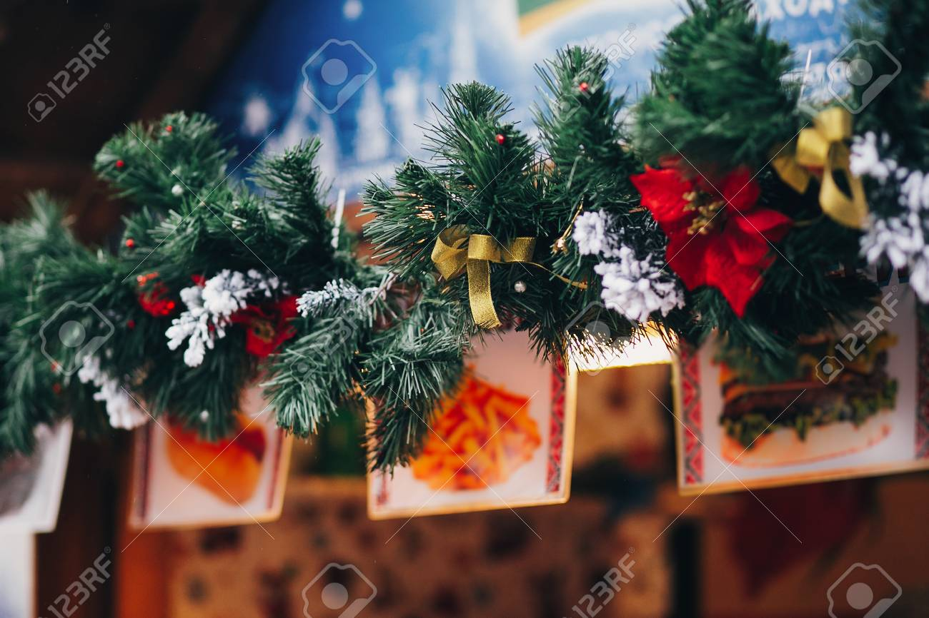 stock photo stylish garland lights and fir branches with christmas decorationsbowssnow on wooden cabins at european city market