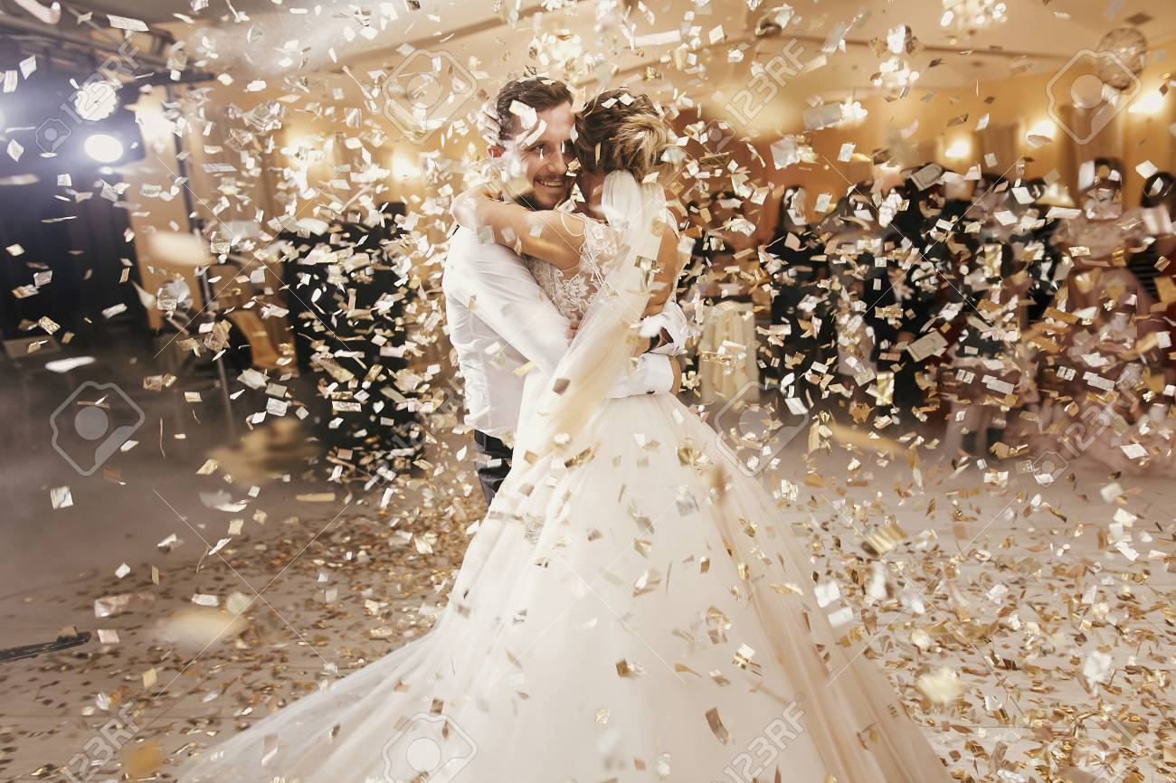 Gorgeous bride and stylish groom dancing under golden confetti at wedding reception. Happy wedding couple performing first dance in restaurant. Romantic moments - 111507962