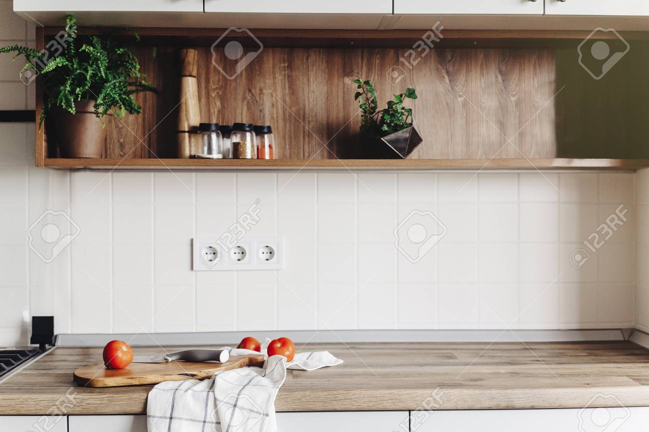 Cooking food on modern kitchen with furniture in grey color and wooden tabletop. Knife on wooden cutting board with vegetables, pepper, spices. Stylish kitchen interior in scandinavian style - 114851521