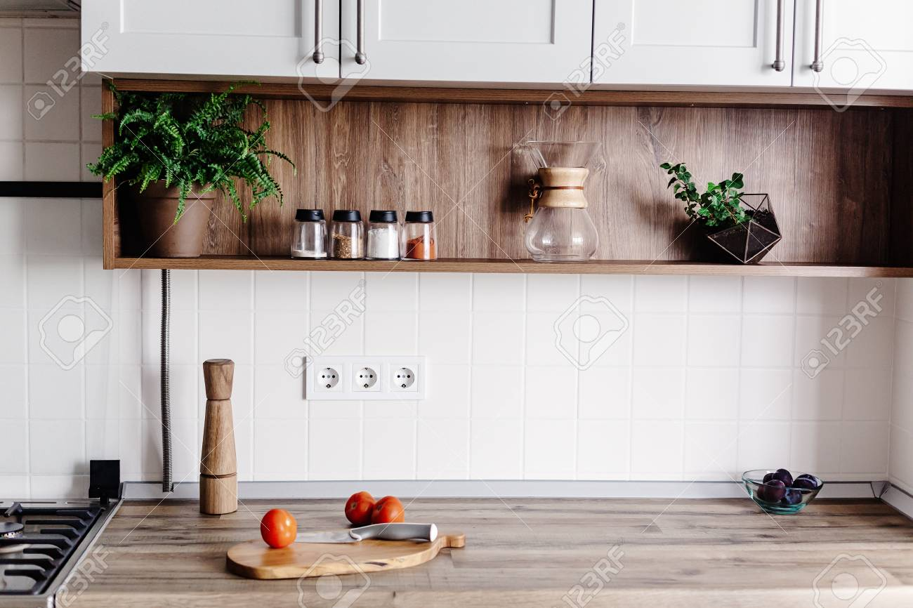 Cooking food on modern kitchen with furniture in grey color and wooden tabletop. Knife on wooden cutting board with vegetables, pepper, spices. Stylish kitchen interior in scandinavian style - 114851761