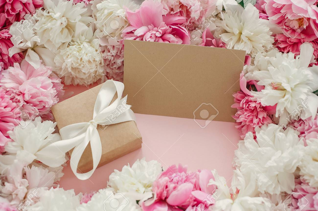 Pink and white peonies with empty card on pastel pink paper