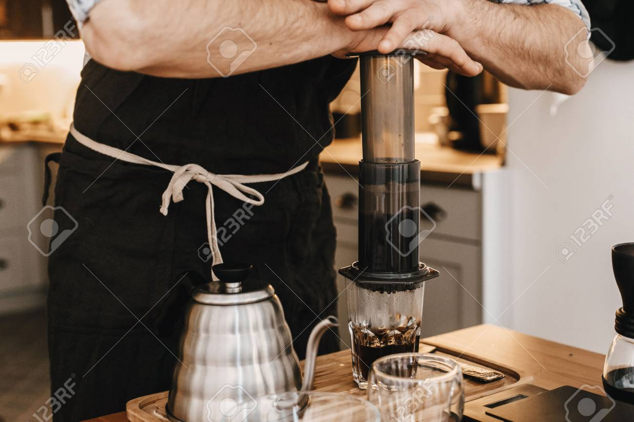 Professional barista preparing coffee in aeropress, alternative coffee brewing method. Hands on aeropress and glass cup, scales, manual grinder, coffee beans, kettle on wooden table - 119391981