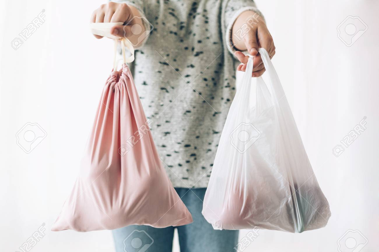 Woman holding in one hand groceries in reusable eco bag and in other vegetables in plastic polyethylene bag. Choose plastic free items. Ban single use plastic. Zero Waste shopping concept. - 120594974