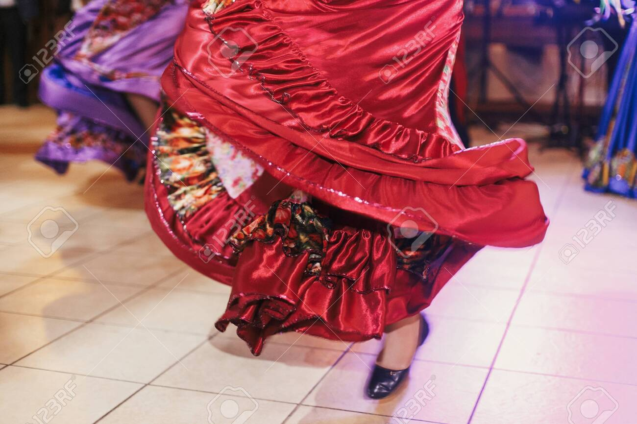 Beautiful gypsy girls dancing in traditional red floral dress