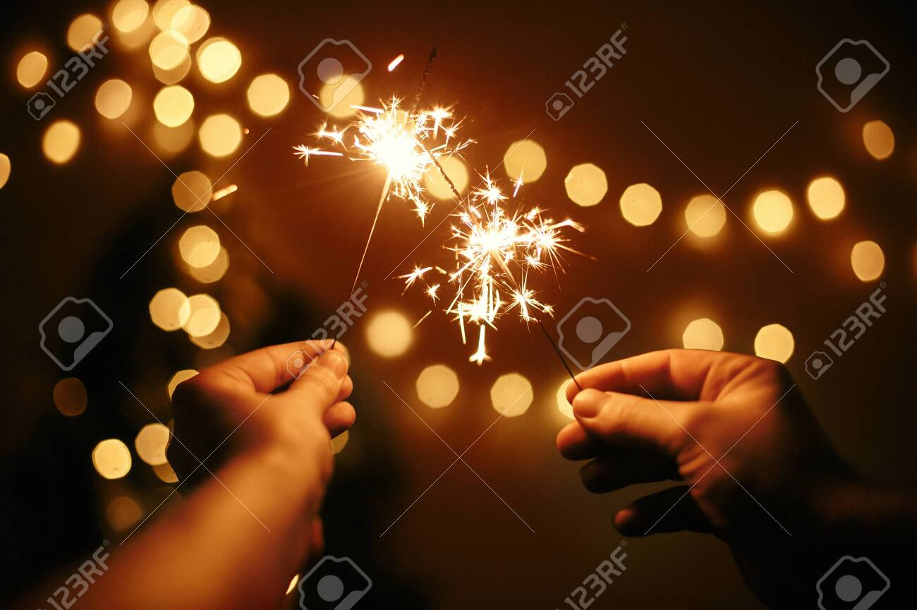 Glowing sparklers in hands on background of golden christmas tree lights, couple celebrating in dark festive room. Happy New Year. Space for text. Fireworks burning in hands. Happy Holidays - 127586424