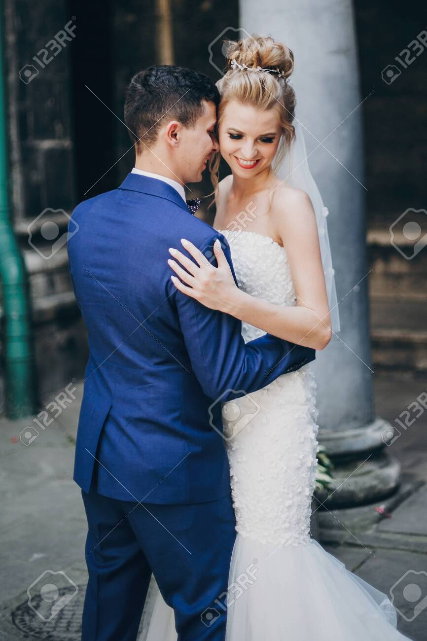 Stylish bride and groom gently hugging in sunny european city street. Gorgeous wedding couple of newlyweds embracing in old buildings. Romantic moment - 128326678