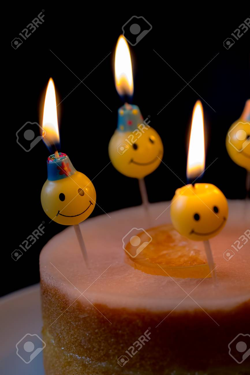 Happy Birthday Cake Candles Smiley Wax Lit Burning On An Orange Frosted