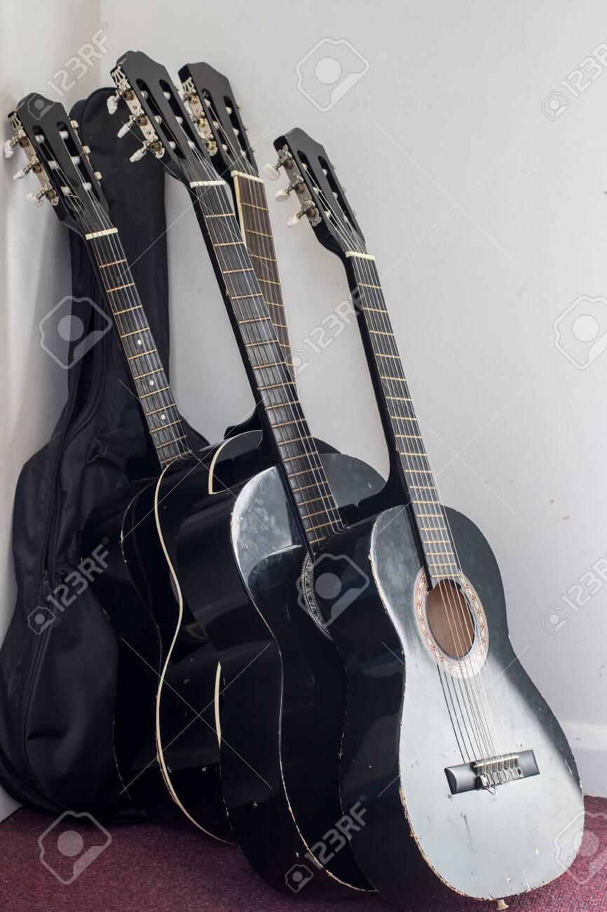 Five black classical guitars leaning against the wall. Student acoustic guitars badly stored in music room. - 139838806