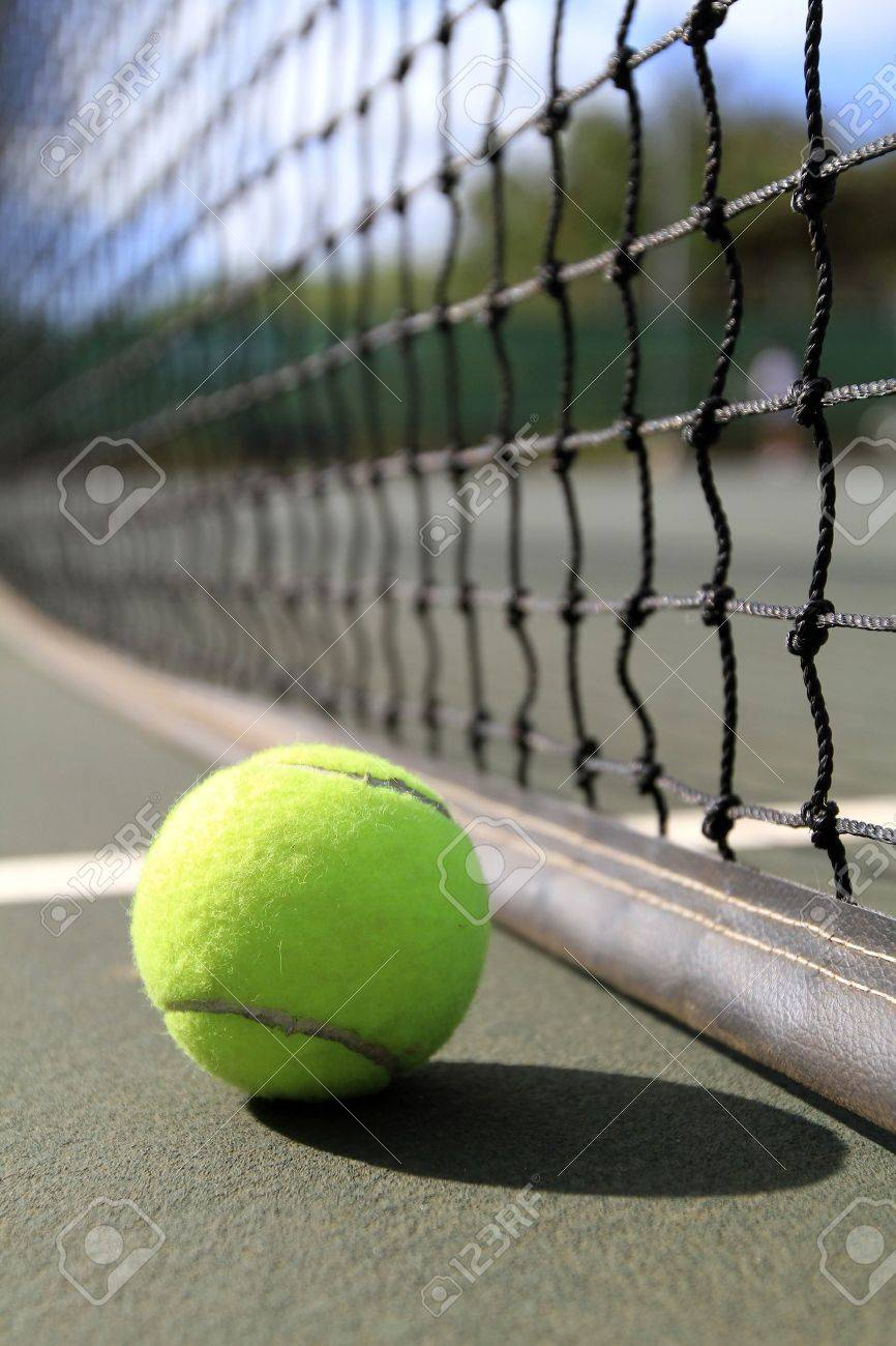 A tennis ball lies on the court next to the net in the daytime Stock Photo - 12144186