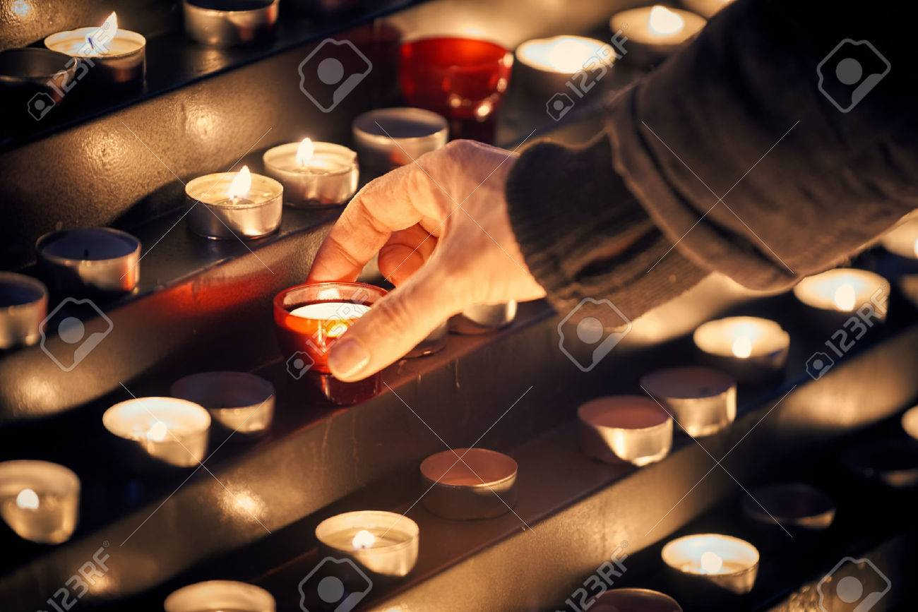 Lighting a candle for someone - Votive church candles in rows - 69066848